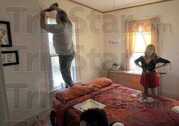 Final details: Tom Moore and Kristy Smith prepare to install curtains in a bedroom as they get ready for an open house Sunday.