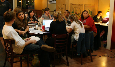 Students study and listen to their classmates perform at the Broad River Coffee Company during open mic night on Wednesday.