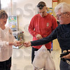Orange Friday: Robin Heng collects cash from Chris Jones and his father Harley Jones at Baesler's Market Friday afternoon.
