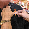 Pinned: Robin Heng pins an orange ribbon onto Harley Jones at Baesler's Market Friday afternoon.