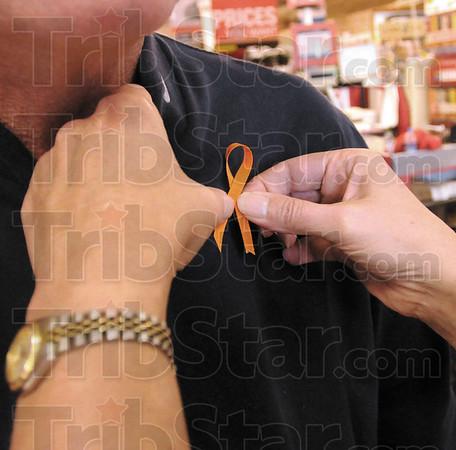 Pinned: Robin Heng pins an orange ribbon onto Harley Jones at Baesler's Market Friday afternoon.