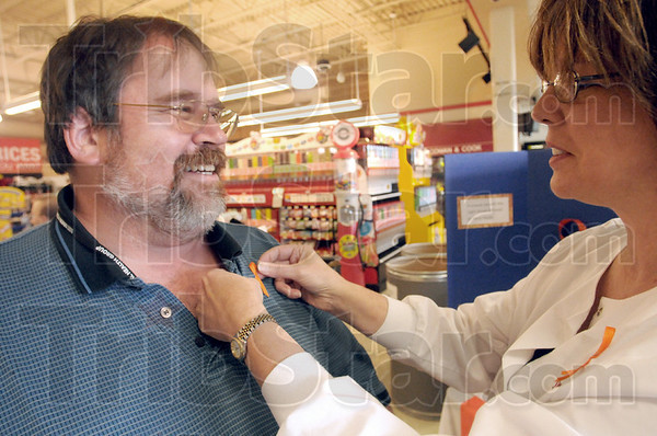 Pinned: Daul Daluga gets an orange ribbon pinned to his shirt by Robin Heng after donating money to the Orange Friday event Friday afternoon at Baesler's Market.