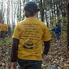 Do my best: A Cub Scout sports a yellow shirt displaying the Cub Scout Promise as he works to remove honeysuckle trees from Dobbs Park Saturday morning.