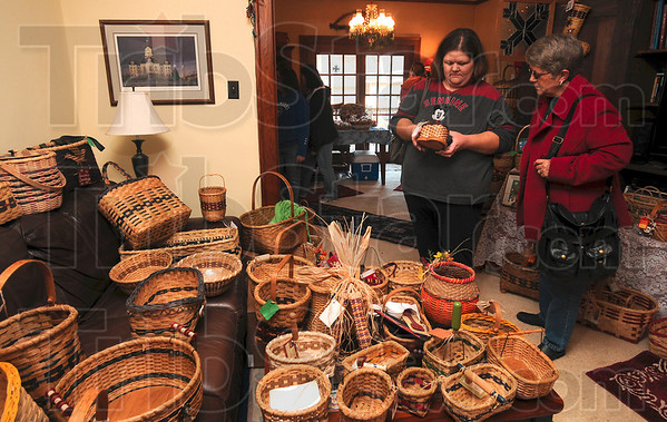 Tribune-Star/Joseph C. Garza<br /> Bounty of baskets: Collett Park Craft Walk patrons Valerie and Lynn Snow admire one of the hand-woven baskets created by Arlene Jennings, Jean Wright, Debbie Rogers and Traci Leburg Saturday in Jennings' home near Collett Park.