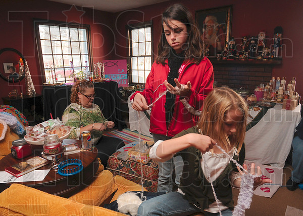 Tribune-Star/Joseph C. Garza<br /> By hand: As Leslie Suttle crafts another piece of her handmade jewelry, sisters Hailey and Isabella Reynolds create finger-knitted scarves for patrons of the Collett Park Craft Walk Saturday on north Tenth Street.