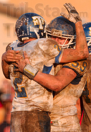 Six points closer to state: Maroa-Forsyth's Justin Barnes hugs teammate Tyler Marsh after the Trojans scored against the Lions Saturday in Marshall.