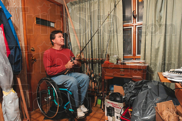 Tribune-Star/Joseph C. Garza<br /> Reel adventure: Don Rogers' experience in the outdoors helped him survive a capsized canoe in alligator infested Florida waters in 2008. Here, Rogers shows off a rod and reel set from his collection in his home Sunday.