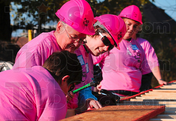 Tribune-Star/Joseph C. Garza<br /> Making a difference: Women Build members, including Marie Hollis, center, work together to build part of the frame at 931 Gilbert Avenue Saturday.