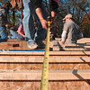 Tribune-Star/Joseph C. Garza<br /> A measure of success: Women Build member Debby Drake measures a part of the frame at 931 Gilbert Avenue during construction Saturday.