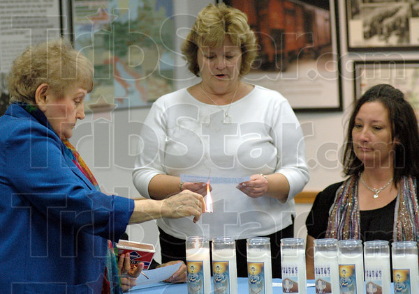Candles: Eva Kor lights a candle as Hoosier Prairie teacher Jeanne Endress reads during a ceremony at the C.A.N.D.L.E.S. Museum Saturday afternoon. West Vigo middle school teacher Donna Neidlinger watches at right.