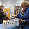 Candles: Chauncey Rose middle school teacher Amanda Davis reads during a candle lighting ceremony Saturday afternoon. At right, Eva Kor lights the candles.