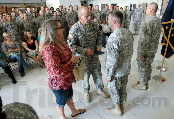 Award: Col. Ivan Denton presents an Indiana Comendation to Master Sgt. Paul Wetnight during a ceremony at Hulman field Saturday. At left is Paul's wife Kimberly.