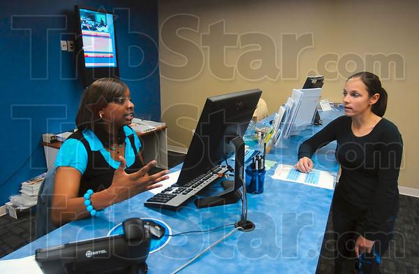 Tribune-Star/Joseph C. Garza<br /> Help(ful) desk: WorkOne employment advisor Jeannette Chatman helps customer Leighann Mendez Wednesday in the renovated WorkOne Western Indiana Service Center on north Eighth Street.