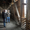 Theft: Mike Roe talks with Tribune-Star reporter Lisa Trigg Wednesday afternoon about the theft of a giant wreath from the side of the Bridgeton covered bridge. Theives removed two planks in the side of the bridge (R) to remove the wreath causing damage.