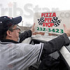 New name: Pizza delivery driver Jeff Cantrell puts the new sign on top of his vehicle as he prepares to make deliveries for the former Ballyhoo Pizza.