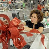 Preparations: Steinmart employee Becky Cummins puts a bow on top of a display that will remain covered until the start of shopping on Black Friday. The secret items will be reduced in price for the sale.