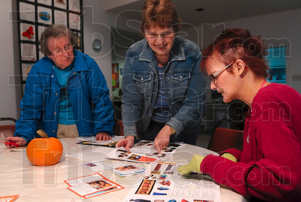 Tribune-Star/Joseph C. Garza<br /> Catalog to the world: Central Christian Church members Nancy Troyer, Mary Jo Brown and Tiffanee Wilson admire the handmade crafts from around the world which are featured in a s SERRV catalog Wednesday at the church.