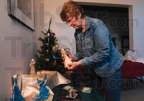 Tribune-Star/Joseph C. Garza<br /> Angels in their places: Central Christian Church member Mary Jo Brown weights down an angel so it will stand on a display Wednesday at the church. The Handmade angels were made in the Philippines and are part of the SERRV International Gift Shop.