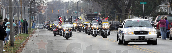 Guard: Citizens line north 13th street as the Patriot Guard escorts the body of Sgt. Dale Griffin to the funeral home Monday morning.