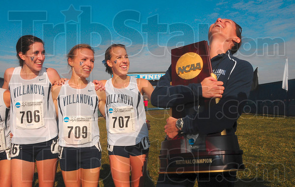 Tribune-Star/Joseph C. Garza<br /> Just to hold it in your arms: Villanova women's cross country coach Gina Procaccio hugs the NCAA Division I National Champion trophy tightly as her runners, Sheila Reid (706), Alison Smith (709)  and Nicole Shappert (707) look on with smiles after the team took first place Monday at the LaVern Gibson Championship Cross Country Course.