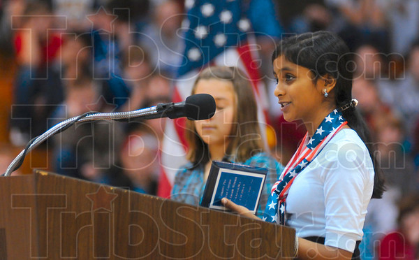Tribune-Star/Joseph C. Garza<br /> An essay about their sacrifice: Honey Creek Middle School student Saagarika Coleman reads her essay about the sacrifice of veterans during a Veterans Day ceremony Tuesday at the school.