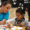 Tribune-Star/Joseph C. Garza<br /> Working together: Indiana State students Kristin Gaither of Indianapolis and Russell Dedeaux of Fort Wayne work with Franklin Elementary kindergartner, Samara Hurtt, as she creates a firefly cookie based on the Eric Carle book, The Lonely Firefly, Tuesday at the elementary school. The Indiana State students were on hand to conduct a literacy fair for the elementary school students and are students themselves in the emergent literacy class at Indiana State University.