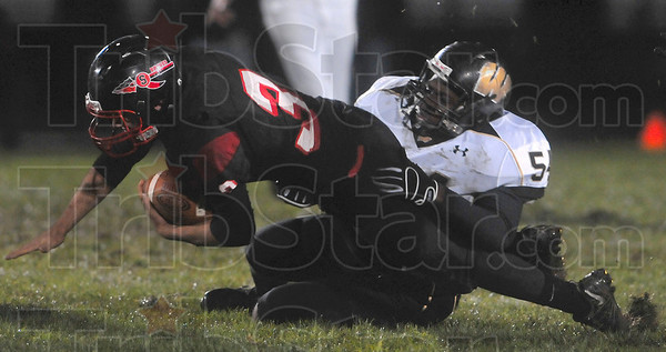 Tribune-Star/Joseph C. Garza<br /> Reach for yardage: Terre Haute South quarterback Bryn Schwartz reaches out for as much yardage as possible as he is tackled by Warren Central's Anthony Brown Friday, Oct. 9 at South.
