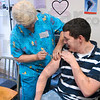 Tribune-Star/Joseph C. Garza<br /> Preventive medicine: Preferred Home Health Care L.P.N. Jane Fields administers an H1N1 vaccination to Indiana University medical student Mike Mooney of Evansville Thursday at the Vigo County Health Department Clinic.