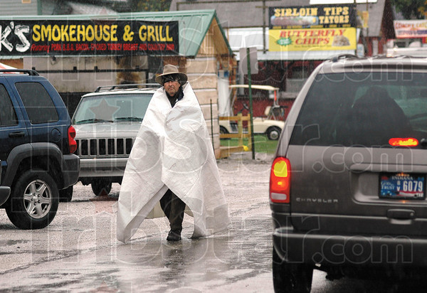 Rain man: A vendor walks along the main street in Bridgeton covered with a tarp Thursday afternoon. The annual Covered Bridge Festival starts Friday morning.