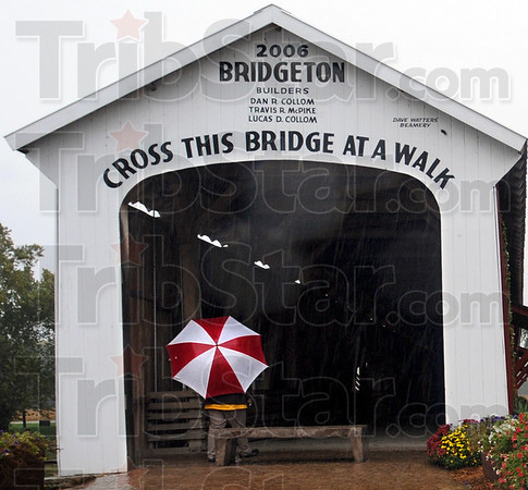 Covered walk: A lone individual walks through the Bridgeton Covered Bridge Thursday afternoon as vendors prepare their booth spaces for Friday's opening of the annual Covered Bridge Festival.