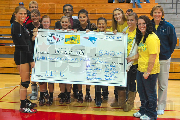 Tribune-Star/Joseph C. Garza<br /> Coming together: Terre Haute South and North volleyball teams came together to raise money for the Union Hospital Neonatal Intensive Care Unit Family Assistance Fund and after all was said and done, raised $8,200 for the unit. Pictured with the giant check are South's Jessica Chichester, coach Steve Beeler, Rayna Gordon, Courtney Hull, Shelby Crncic, Dr. Russel Coutinho, Larina Coutinho, North's Bri Hill, Sara Baugh, Katie Behnke, Kelbie Drebes and coach Kris Painter.