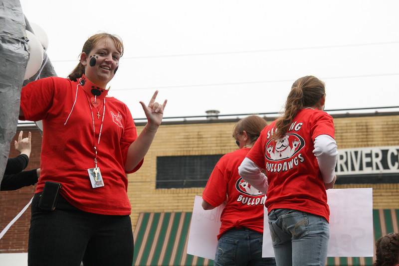 A Deaf Club member shows off the club sign while riding the float during the Homecoming day parade on Saturday.