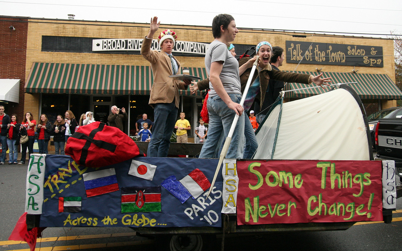 """The Honors Student Association encourages the crowd to """"go green"""" from their float during the Homecoming day parade on Saturday."""