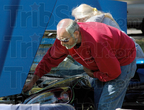 Clean machine: Tom Peter wipes the dust from the engine compartment of his wife's Corvette as they prepare it for judging at the Old Fashioned Days event at Collett Park Sunday afternoon.