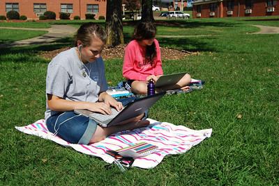 Elisa Beekman and Jessica Greer study on the quad.