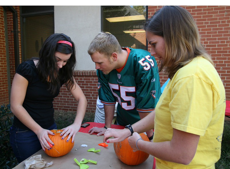 (L-R) Lori Norman (sophomore), Brian Arnold, and Amy Brethauer (sophomore) work on their pumpkin designs during the pumpkin carving contest sponsored by SGA Thursday afternoon as part of the 2009 Homecoming festivities.