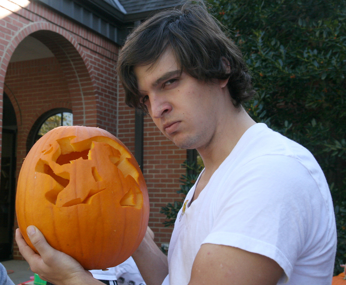 """Taylor Doolittle (junior) poses with his """"headless horseman"""" design during the pumpkin carving contest sponsored by SGA Thursday afternoon as part of the 2009 Homecoming festivities."""