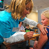 Tribune-Star/Joseph C. Garza<br /> Steel sisters: Sugar Creek Consolidated Elementary School student Paige Buckallew, 10, didn't flinch or cry as she received an H1N1 influenza vaccination from Preferred Home Health Care RN Dana Garcia Friday at the school in West Terre Haute. Looking on is Buckallew's younger sister, Gabby, 7, who didn't flinch either when she received her shot.