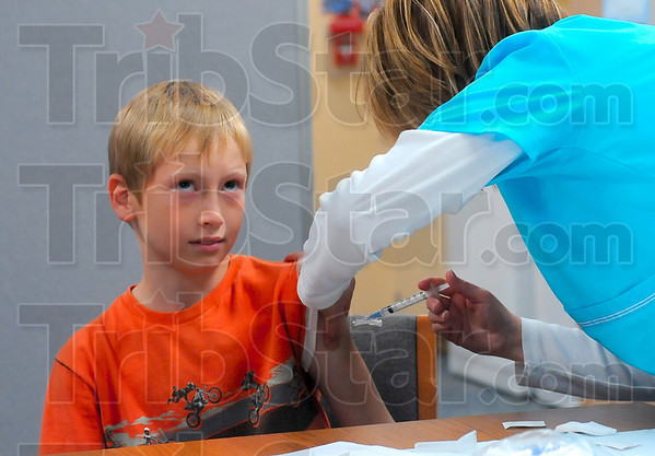 Tribune-Star/Joseph C. Garza<br /> Concentrate, concentrate...: Sugar Creek Consolidated Elementary third-grader John Michael McClain focuses on a television program as Preferred Home Health Care RN Dana Garcia administers an H1N1 vaccination Thursday the school.