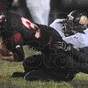 Tribune-Star/Joseph C. Garza<br /> Reach for yardage: Terre Haute South quarterback Bryn Schwartz reaches out for as much yardage as possible as he is tackled by Warren Central's Anthony Brown Friday at South.