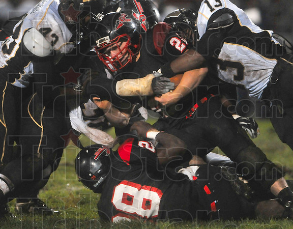 Tribune-Star/Joseph C. Garza<br /> Just one more yard: Terre Haute South's PJ Montgomery struggles for another yard as he is collides with the Warren Central defense Friday at South.
