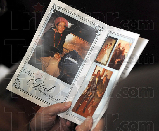 With God: A woman attending the memorial service for Bettie Davis holds the Obituary and photos from Bettie's life.