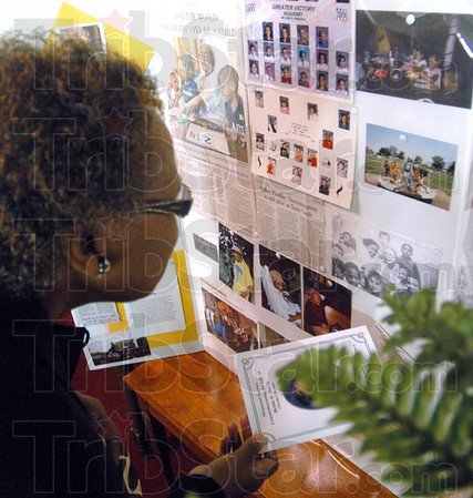 Life and times:  Jeanette Smith looks a a board of photographs prior to the start of the memorial service for Bettie Davis at the Allen Chapel Saturday afternoon.