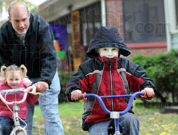 Cruisin': Four-year-old Garin Monson cruises along the sidewalk in front of his northside home Friday afternoon followed by his dad Christian and sister Azabelle.