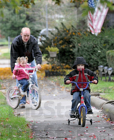 Training wheels: Christian Monson watches son Garin ride ahead as he helps two-year-old daughter Azabelle.
