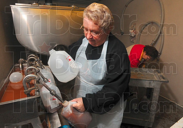 Tribune-Star/Joseph C. Garza<br /> In demand: Ditzler Orchard employees Paula Blair and Nancy Loomis, both of Rosedale, work in tandem to fill gallon jugs with apple cider Monday in the orchard's cider room.