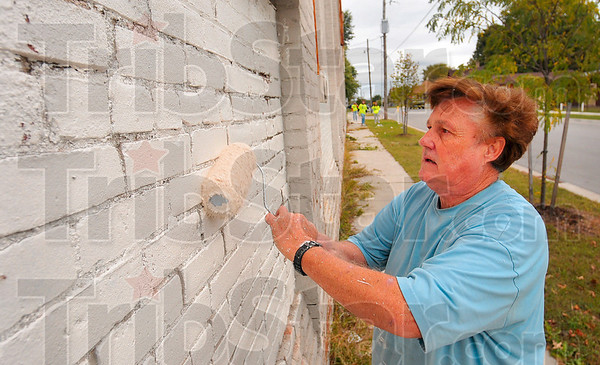 Tribune-Star/Joseph C. Garza<br /> Wiping it out: Volunteer Larry Fivecoat helps paint over graffiti on a building off of Wabash Avenue during an effort by volunteers to wipe out graffiti around the city Saturday.