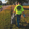 Tribune-Star/Joseph C. Garza<br /> In search of...trash!: Walmart department manager Ed Gillie walks around the Booker T. Washington center with other Walmart volunteers in search of trash during an effort to clean the area Saturday.