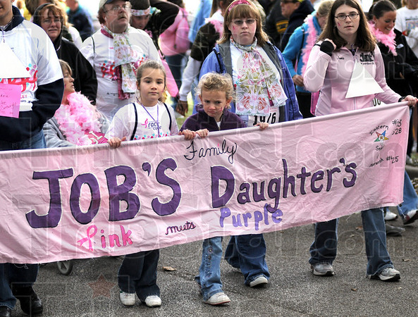 "Banner day: Participants in the Race for the Cure ""fun walk"" carry a banner down the main route of the event Saturday morning."