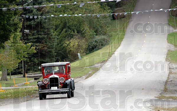 Upside-down: A vintage auto drives down the Newport Hill as it arrives for the annual event Friday afternoon. The Hill Climb celebrates its 100th anniversary this year.